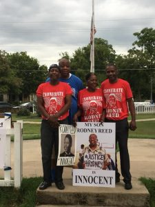Richard Reed, Ryan Reed, Mama, Rodrick Reed, poster of Daddy, and high school photo of Rodney Reed at rally.